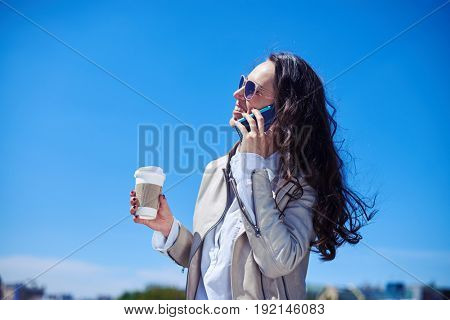 Mid shot of marvelous brunet talking on phone while drinking coffee on top of building
