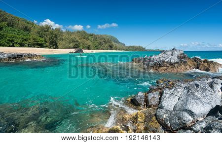 Rocks frame the turquoise ocean with surfer on board off Lumahai Beach in Kauai in Hawaiian islands
