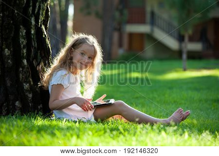 Child with tablet pc outdoors. Little girl on grass with computer