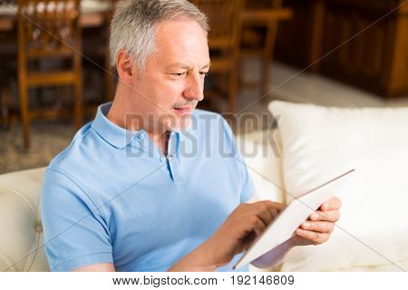 Mature man using a tablet at home