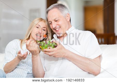 Mature couple eating a salad in the living room.