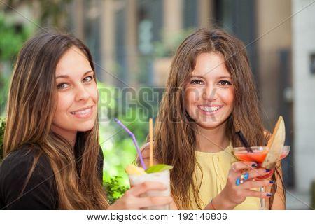 Two girls having an aperitif outdoor
