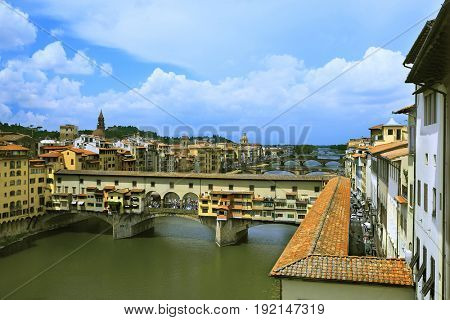 embankment of Arno river in Florence, Italy with Ponte Vecchio bridge over the river