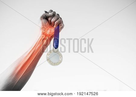 Cropped hand of sportsperson holding gold medal against clear sky