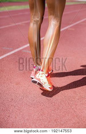 Low section of athlete walking on track during sunny day