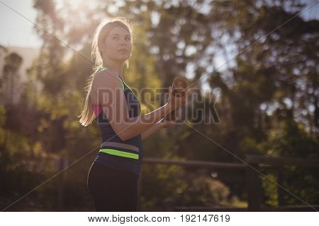 Woman carrying wooden log during obstacle course in boot camp