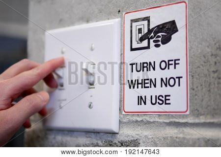 Woman preparing to turn off light switch by saving power concept