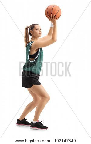 Full length profile shot of a young woman throwing a basketball isolated on white background