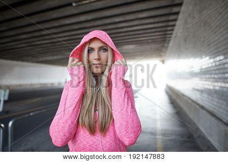 Female runner training in city tunnel, wearing pink hoody.