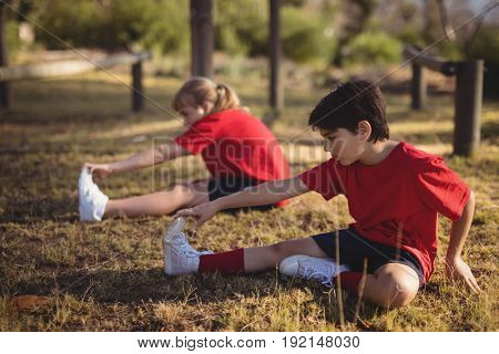 Kids performing stretching exercise during obstacle course in boot camp
