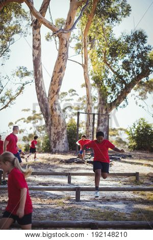 Trainer instructing kids during obstacle course training in the boot camp