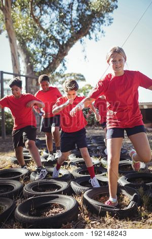 Kids running over tyres during obstacle course training in the boot camp