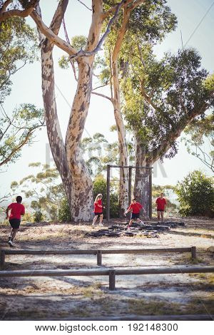 Group of kids running over tyres during obstacle course training in the boot camp