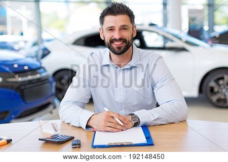 Confident young car dealer in showroom