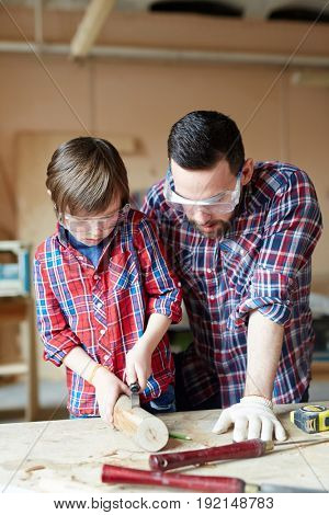 Little boy woodcrafting while his father consulting him
