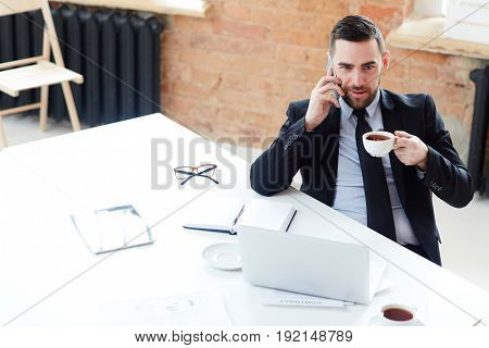 Elegant man with cup of tea sitting by workplace and calling