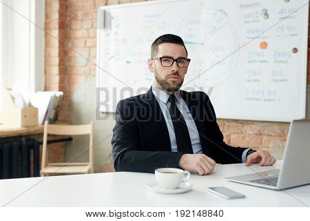 Serious trader sitting by workplace in office