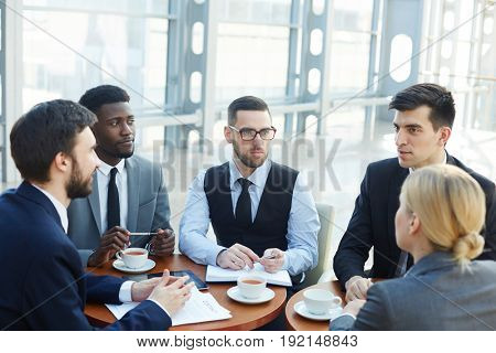 Group of modern business people meeting in office building discussing work