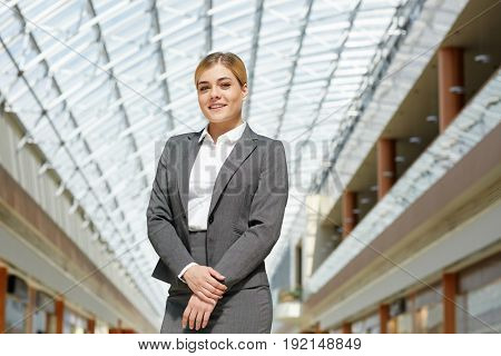 Portrait of confident young businesswoman posing looking at camera in modern office building under glass roof