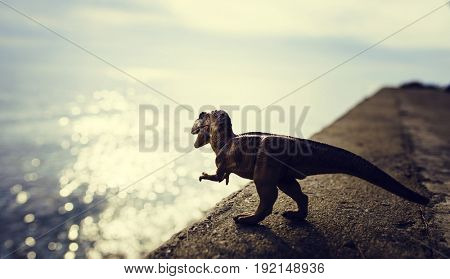 T Rex Dinosaur Toy Model Standing Next To Ocean