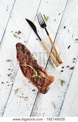 Restaurant Grilled Food - Delicious Grilled Striploin Steak. Gourmet Restaurant Steak Menu. Steak Served on White Wooden Background