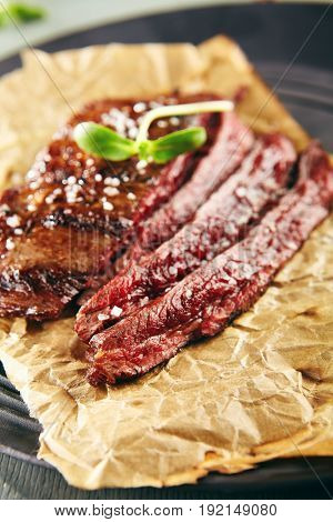 Restaurant Grilled Food - Delicious Grilled Flank Steak. Gourmet Restaurant Steak Menu. Flank Steak Served on Parchment with Green Herbs