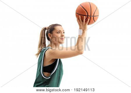 Young woman in a green jersey throwing a basketball isolated on white background
