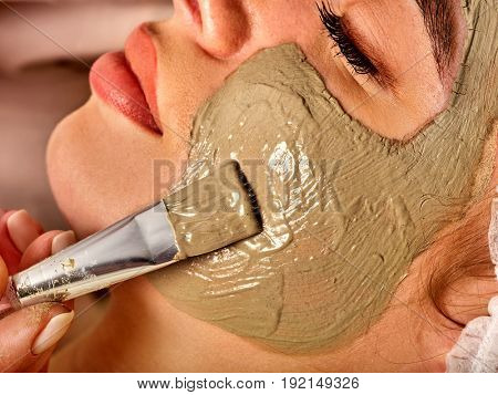 Mud facial mask of woman in spa salon. Massage with clay full face. Girl on with therapy room. Beautician with brush therapeutic procedure . Therapeutic mud for home masks.