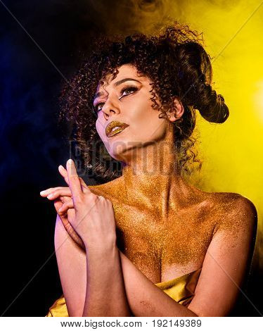 Golden powder cosmetics on bare woman shoulders with decorative. Girl with curls on dark background. Woman at disco In gold mystical fog. Visions of drug addict. Witch going to Sabbath.