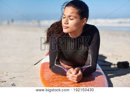 Woman surfer in wetsuit lying on her surfboard enjoying the sunshine, relaxing between surf sessions
