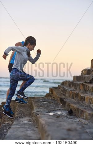 Fit strong couple sprints up steps by the ocean, intense exercise fitness workout