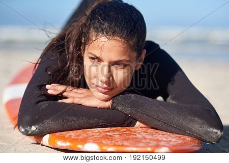 Portrait of beautiful woman surfer in wetsuit, lying on surfboard on beach, relaxed travel vacation holiday