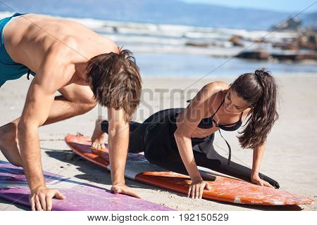 surf instructor demonstrating how to stand up on surfboard in private surf class