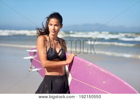 Fit athletic surfer girl holding surf board on the beach, sunny day blue skies waves in background