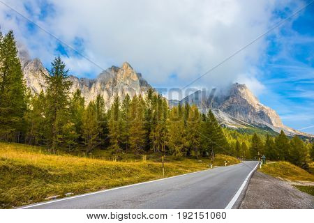 Asphalt road at the foot of the mountains. The concept of ecological tourism. Sharp rocks surround the grassy valleys. The dizzying Dolomites