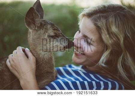 Woman and young animal. Young woman taking care of deer fawn. Human and animal leaving in harmony.