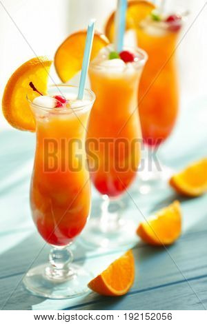 Glasses of Tequila Sunrise cocktail with orange slices on blue table