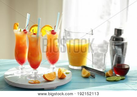Glasses of Tequila Sunrise cocktail with citrus slices on table