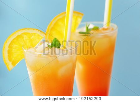Glasses of Tequila Sunrise cocktail with orange slices on blue background, closeup