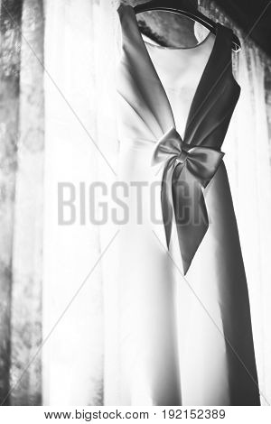 Closeup of White Wedding Dress Hanging by the Window Grayscale