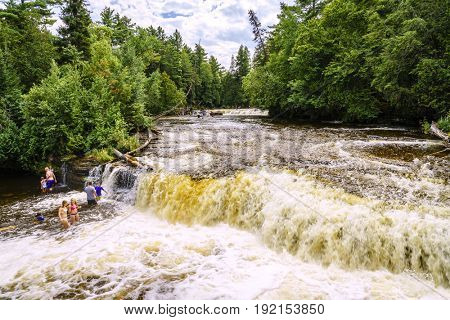 Tahquamenon Falls State Park. Michigan, August 9, 2016: Vacationers are swimming in Lower Tahquamenon Falls on a beautiful summer day