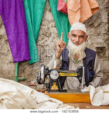 Leh, Ladakh, India, July 12, 2016: a tailor is working at his shop on a small street in Leh, India