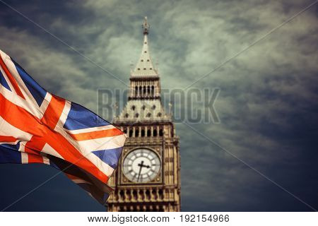 close up of Big Ben Clock Tower and Union Jack flag Against Blue Sky England United Kingdom