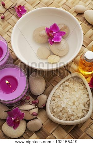 SPA still life with bowl of water, bath salt, aromatherapy candle and orchid flowers