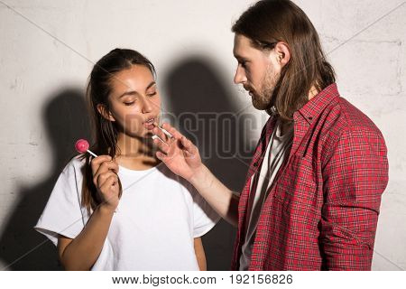 Young hipster man standing over gray background give cigarette to girlfriend holding candy.