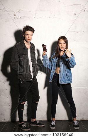 Image of young hipster woman standing over gray background near boyfriend holding chocolate showing middle finger.