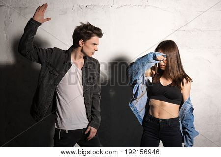 Photo of angry young hipster man tries to strike his girlfriend over gray background