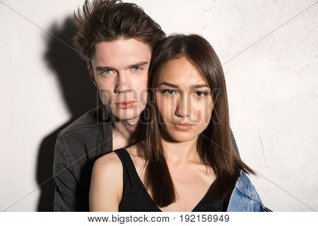 Picture of serious young hipster loving couple looking at camera over gray background