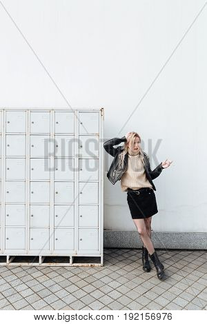 Fashion portrait of angry young blonde lady standing near safes. Looking aside holding cigarette.