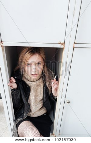 Fashion portrait of serious young blonde lady sitting in safe. Looking at camera holding cigarette.